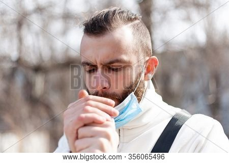 A Guy In An Antiviral Mask Takes Off And Smokes A Cigarette On The Street.