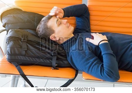 A Passenger Is Waiting For His Plane At The Airport. A 35-40 Year Old Man Sleeps On A Bench While Wa