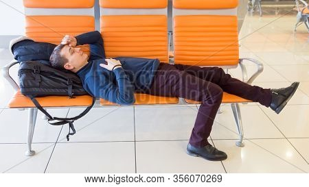 A 35-40 Year Old Man Sleeps On Bench While Waiting For His Flight At The Airport. A Passenger Is Wai