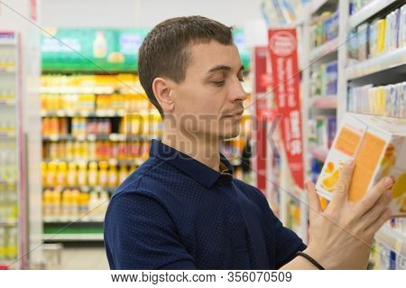 A Young Man Chooses A Product In A Store. A 30-35-year-old Man In A Blue T Shirt Looks And Selects G