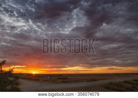 Marree Crossroads With Dramatic Clouds, Orange And Purple Summer Sunset And Copy Space, Taken In The
