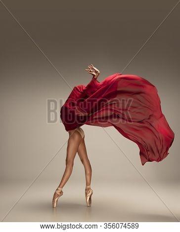 Free Flight. Graceful Classic Ballerina Dancing On Grey Studio Background. Deep Red Cloth. The Grace