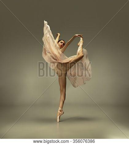 Spring Blooming. Graceful Classic Ballerina Dancing On Grey Studio Background. Tender Beige Cloth. T