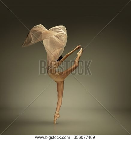 Soft Touch. Graceful Classic Ballerina Dancing On Grey Studio Background. Tender Beige Cloth. The Gr