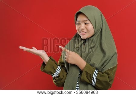 Young Beautiful Muslim Woman Showing Blank Copy Space. Cute Young Muslim With Welcome Gesture. Musli