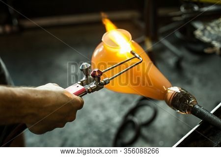 A Close Up Selective Focus Shot On The Hands Of A Glassmaker At Work On A Blown Glass Lantern, A Glo