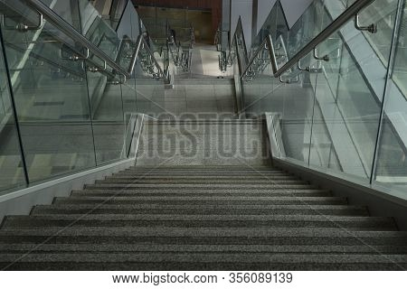 Gray Marble Staircase With Metal Railing In A Shopping Center Or Hospital. Glass Railing. Close-up.