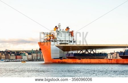 Seascape Side View Of A Large Orange Semi-submersible Heavy-lift Ship With Large Load Entering Harbo