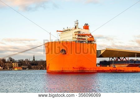 Seascape Closeup Side View Of A Large Orange Semi-submersible Heavy-lift Ship With Large Load Enteri