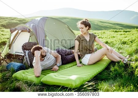 Young And Cheerful Couple Lying On The Mattress At The Campsite, Enjoying Summer Time While Travelin