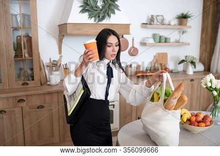 Young Woman Coming Home After Work With Shopping Bag