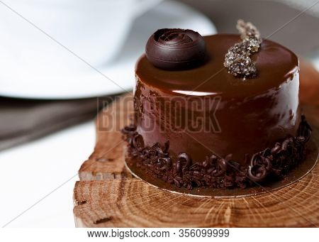 Chocolate Cake Stands On A Decorative Wooden Plate Next To A White Cup Of Coffee
