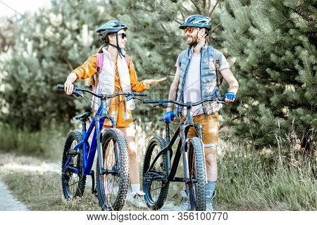 Young Couple Dressed Casually Talking Together While Traveling With Mountain Bicycles On The Forest