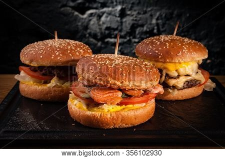 Menu Of Different Burgers On One Board. Side View Of A Fish Burger, Hamburger And Cheese Burger, Aga