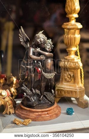 Vertical Picture Of Objects In Showcase Of Antiquarian Shop With Small Figure Of Two Cupidons And Ca