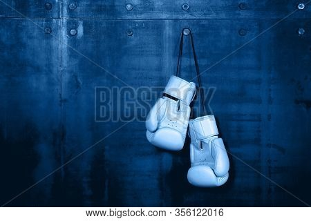 Close Up Pair Of Clasic White Leather Boxing Gloves Hanging Over Dark Blue Wall With Copy Space