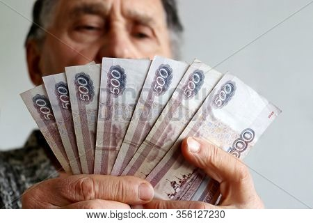 Elderly Man Counts Russian Rubles In Hands. Pension Payments, Retirement Savings Or Benefits Concept