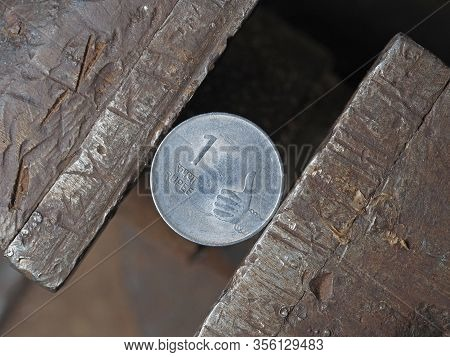 Indian Rupee Coin Clamped In A Metal Vise On Both Sides. The Concept Of Financial Pressure On The Cu