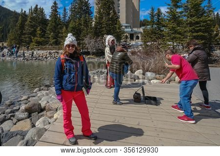 Lake Louise - May 20 2019: Lake Louise, Alberta, Canada. Girl Is Posing In Front Of Tourists With An