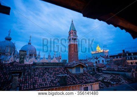 San Marco Campanile and Saint Mark's Basilica in Venice on Sunrise. City's Roofs.