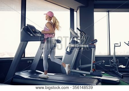 Side View Of Sexy Sporty Blonde Woman In Pink Cap Exercising On Treadmill In Gym.