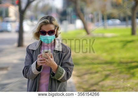 Woman Wearing Medical Mask In Street In City And Speaks On The Phone. Woman Walking On The Street We