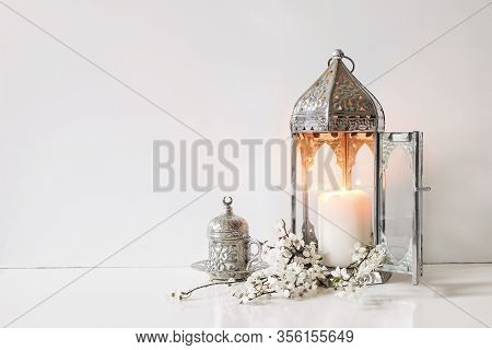 Silver Decorative Cup Of Tea, White Flowers, Prunus Tree Blossoms And Glowing Moroccan Lantern On Ta