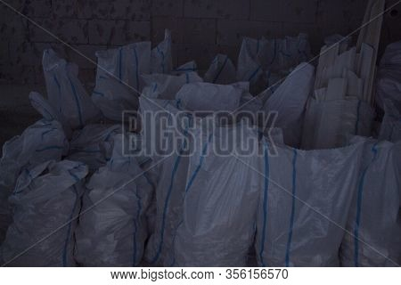 White Construction Bags Of Construction Debris In A Pile. Pollution Concept. A Pile Of Garbage In A