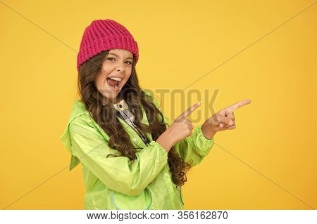 Best Buy. Little Girl Point Fingers At Something Yellow Background. Happy Child Presenting Product.