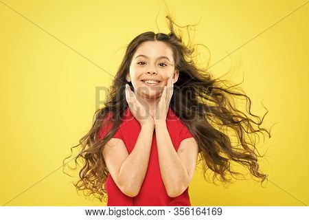 Girl Adorable Kid Long Wavy Hair Yellow Background. Wind Can Also Damage Hair. Strong Persistent Win