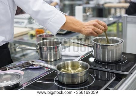 Professional Chef Workplace At Cuisine Of Restaurant. Close Up View Of Man Hand Stirring Soup With S