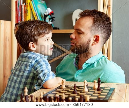 Father And Son Child Playing Chess At Home
