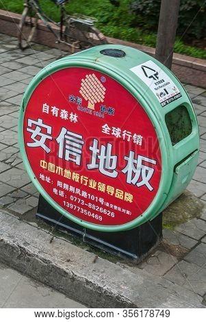 Guilin, China - May 10, 2010: Downtown. Closeup Of Red And Green Trash Receptacle In Street. Mandari