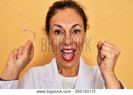 Middle age senior dentist woman holding clear aligner for teeth correction screaming proud and celebrating victory and success very excited, cheering emotion