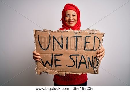 Woman wearing muslim hijab asking for union holding banner with united stand message with a happy face standing and smiling with a confident smile showing teeth