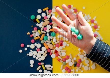 Top View Of Child Hand Holding Tablet Pills Against Colorful Background. Many Tablets, Pills, Medici