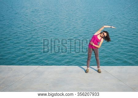 Woman Warming Up Before Jogging. The Girl Is Stretched On The City Promenade. Training In The City.