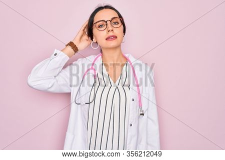 Beautiful doctor woman with blue eyes wearing coat and stethoscope over pink background confuse and wonder about question. Uncertain with doubt, thinking with hand on head. Pensive concept.