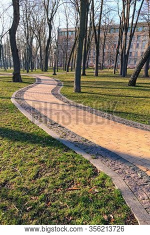 Beautiful Early Morning In The Park. Winding And Narrow Gray Stone Walkway. Deserted Alley Between B