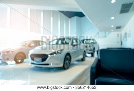 Blurred Front View Of White Car And Customer. New Luxury Car Parked In Modern Showroom. Car Dealersh
