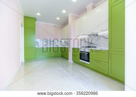 New Kitchen Set In Green And White Colors In The Style Of Minimalism In A New Building. The Top Unde