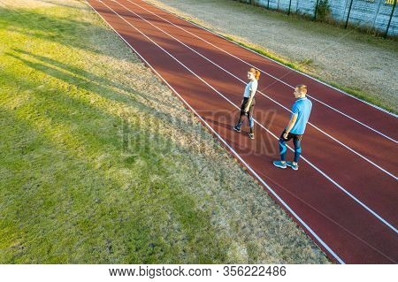 Top Down Aerial View Of Two Young People Sportsman And On Red Rubber Running Track Of A Stadium Fiel