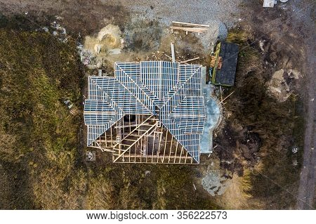 Private Residential House With Wooden Roof Frame Structure Under Construction. Unfinished Brick Buil