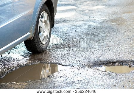 Close Up Of Car Wheel On A Road In Very Bad Condition With Big Potholes Full Of Dirty Rain Water Poo