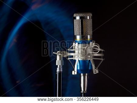 Metal Microphone On A Blue Fire Line And Dark Background Photo