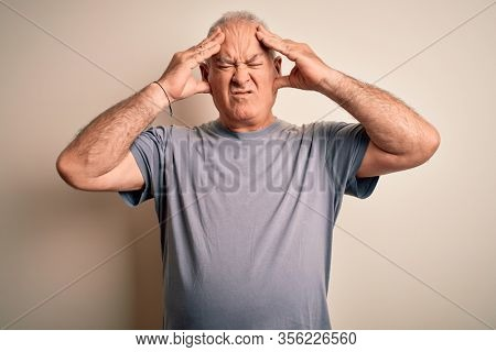 Middle age handsome hoary man wearing t-shirt standing over isolated white background suffering from headache desperate and stressed because pain and migraine. Hands on head.