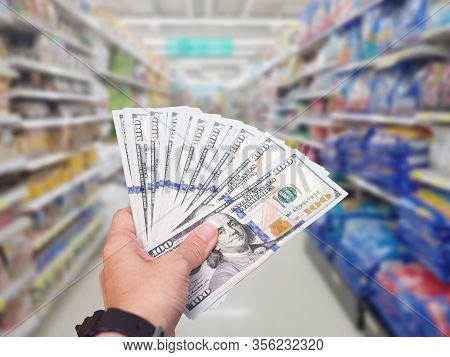 Hand Hold American Dollar Usd Banknote At Shopping Store Blur Background.coronavirus Covid-19 Spread