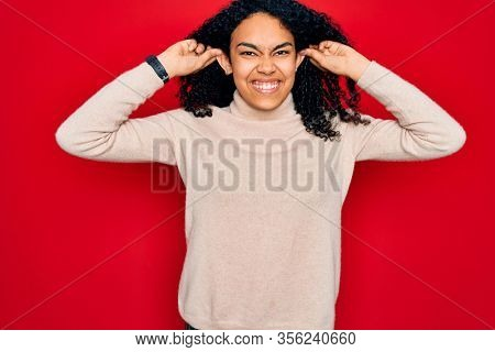 Young african american curly woman wearing casual turtleneck sweater over red background Smiling pulling ears with fingers, funny gesture. Audition problem