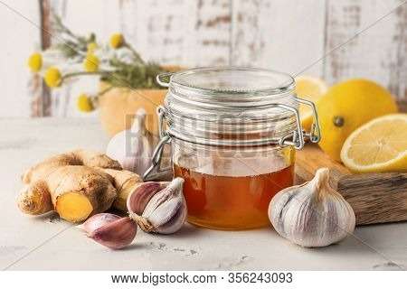 Alternative Medicine, Natural Home Remedy For Cold And Flu. Glass Jar With Honey, Ginger, Lemon, Gar