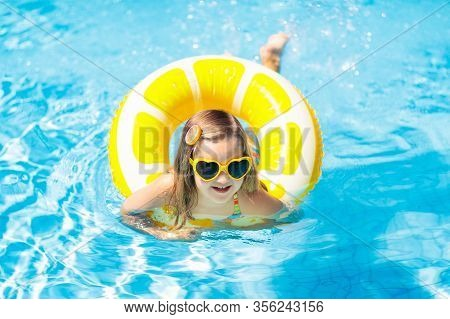 Child In Swimming Pool On Inflatable Yellow Lemon Ring. Little Girl Learning To Swim